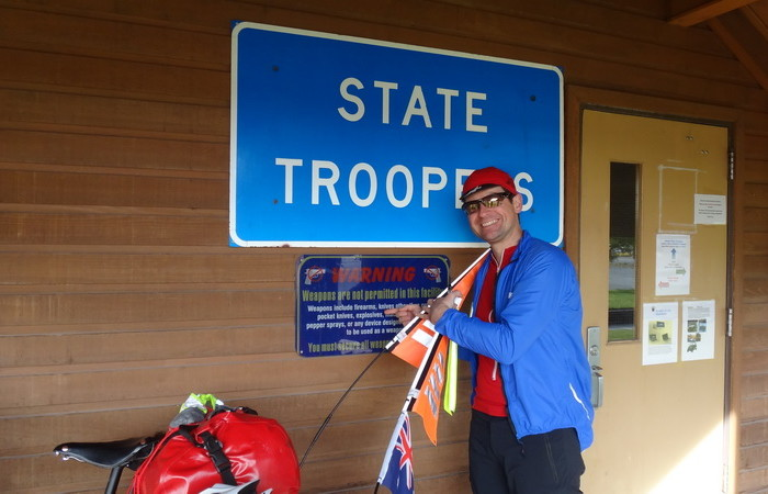 Day 9 - David outside the State Troopers office in Tok trying to hand in the gun ... but you can't bring guns inside ....