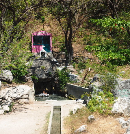 Oaxaca Coast - Locals bathing in a spring below a pink roadside shrine