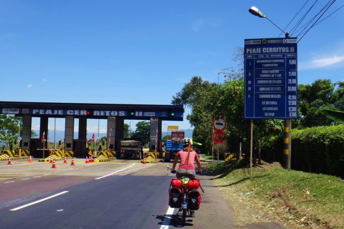 Colombia - Jo cycling towards one of the many toll booths - bikes pass for free
