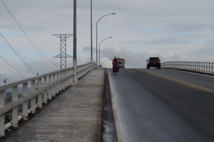 Guatemala - Jo cycling over the Rio Dulce Bridge